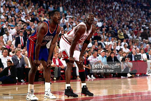 Joe Dumars of the Detroit Pistons awaits a freethrow with Michael Jordan of the Chicago Bulls in 1990 during the NBA game at Chicago Stadium in...