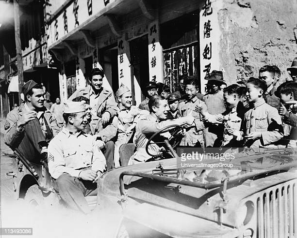 Joe E Brown American actor and comedian driving jeep loaded with American GIs seeing the sights in China Brown giving thumbs up sign to Chinese...
