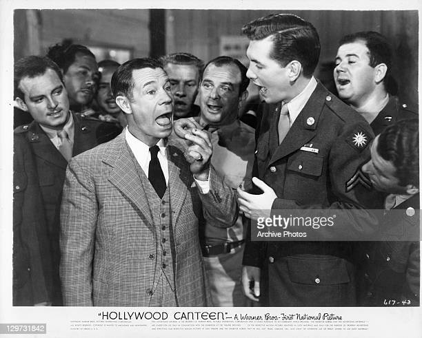 Joe E Brown eating donut in front of group of unidentified men in a scene from the film 'Hollywood Canteen' 1944