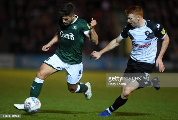 Joe Edwards of Plymouth Argyle is tackled by Rory Gaffney of Salford City during the Sky Bet League Two match between Plymouth Argyle and Salford...