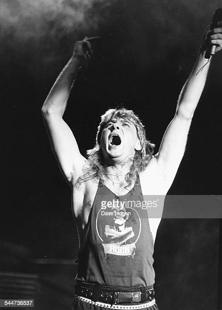 Joe Elliot lead singer with the band 'Def Leppard' with his arms raised to the sky as he performs on stage in Sheffield England October 9th 1987