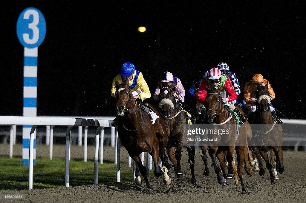 Joe Fanning riding Into Wain (red sleeves) turn into the straight to win The 32Red Handicap Stakes at Kempton racecourse on November 22, 2012 in Sunbury, England.