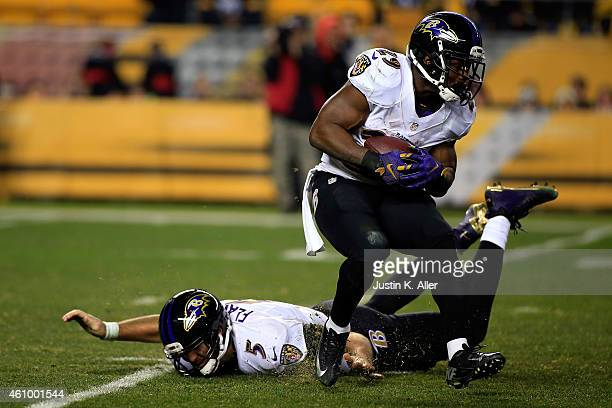 Joe Flacco falls to the ground after handing the ball to Justin Forsett of the Baltimore Ravens against the Pittsburgh Steelers during their AFC Wild...