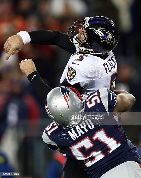 Joe Flacco of the Baltimore Ravens gets tackled after a throw against Jerod Mayo of the New England Patriots during the 2013 AFC Championship game at...