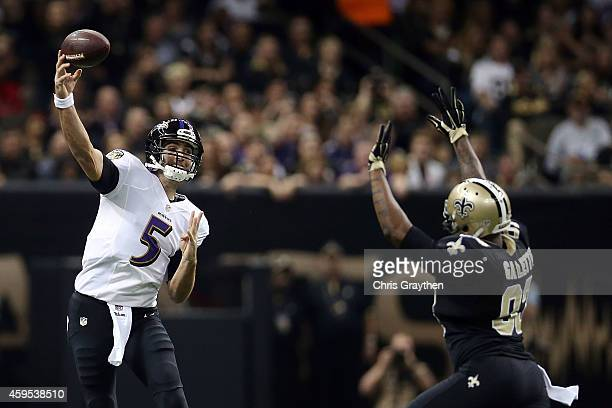 Joe Flacco of the Baltimore Ravens is pursued by Junior Galette of the New Orleans Saints during the first quarter of a game at the MercedesBenz...