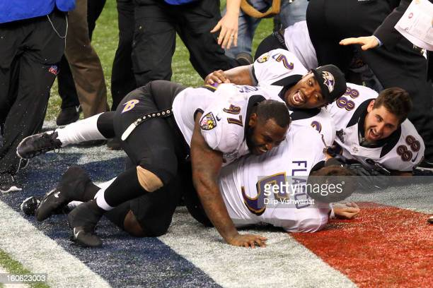 Joe Flacco of the Baltimore Ravens is tackled while celebrating with teammates Arthur Jones, Tyrod Taylor, and Dennis Pitta following their 34-31 win...