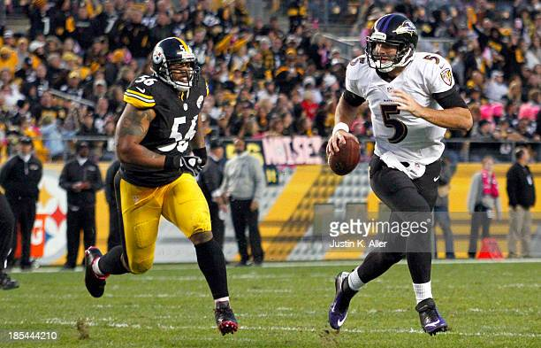 Joe Flacco of the Baltimore Ravens scrambles out of the pocket against LaMarr Woodley of the Pittsburgh Steelers during the game on October 20 2013...