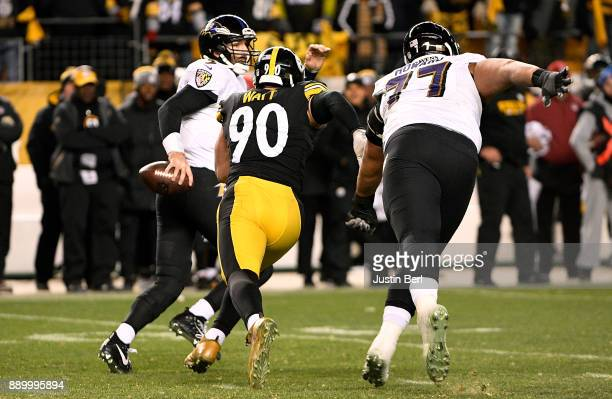 Joe Flacco of the Baltimore Ravens scrambles to avoid the oncoming rush of TJ Watt of the Pittsburgh Steelers in the fourth quarter during the game...