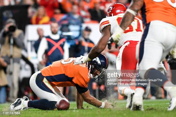 Joe Flacco of the Denver Broncos loses the ball after being hit by Frank Clark of the Kansas City Chiefs as Alex Okafor closes in during the third...
