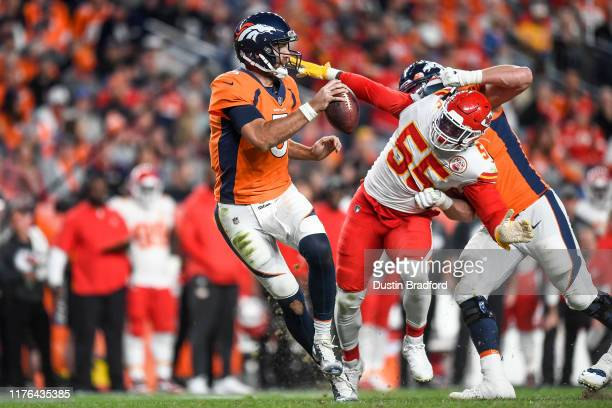 Joe Flacco of the Denver Broncos scrambles before being sacked by Frank Clark of the Kansas City Chiefs in the third quarter at Empower Field at Mile...