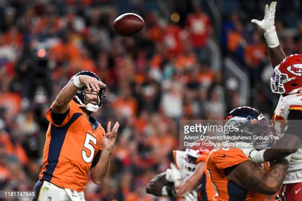 Joe Flacco of the Denver Broncos throws as Emmanuel Ogbah of the Kansas City Chiefs prepares to bat the ball down at the line during the third...