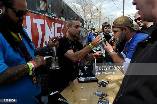 Joe Flores right loads a hit of wax for a client to sample during the High Times US Cannabis Cup at the Exdo Center in Denver Colorado on Saturday...