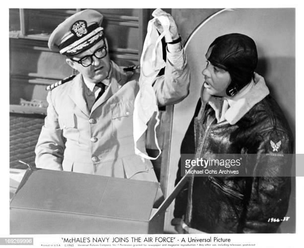 Joe Flynn holding up bra in front of a dumb founded Tim Conway in a scene from the film 'McHale's Navy Joins The Air Force' 1965