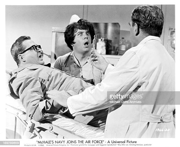 Joe Flynn struggles to get away from Nelson Olmsted's needle as 'nurse' Tim Conway reacts in a scene from the film 'McHale's Navy Joins The Air...