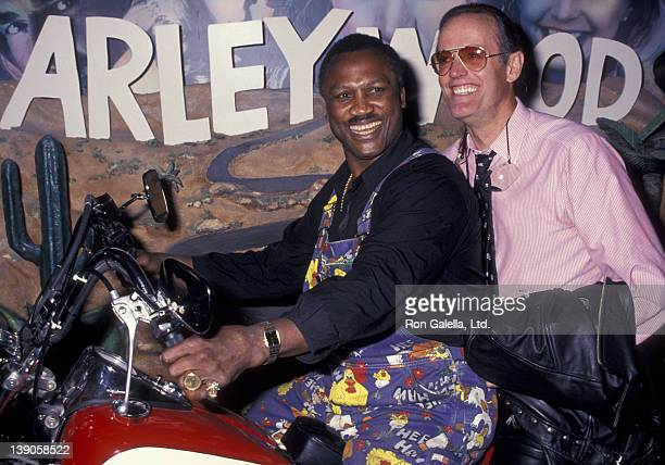 Joe Frazier and Peter Fonda attend the grand opening of the HarleyDavidson Cafe on October 19 1993 in New York City