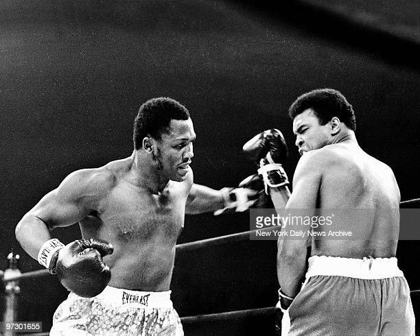 Joe Frazier gets off in his customary smoking style and fires sweeping left hook as Muhammad Ali gets up right to fend off blow