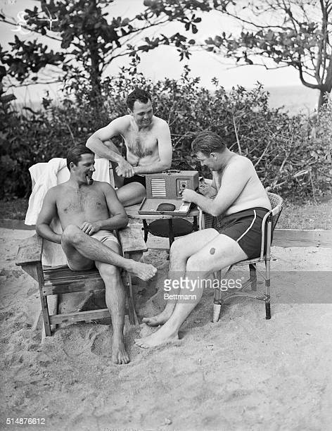 Joe Gallagher Ducky Medwick and Louis Riggs listen to a New York radio broadcast as they enjoy some relaxation time at the beach of the Hotel Nacional