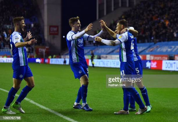 Joe Garner of Wigan Athletic celebrates with his team mates as he scores a penalty during the Sky Bet Championship match between Wigan Athletic and...