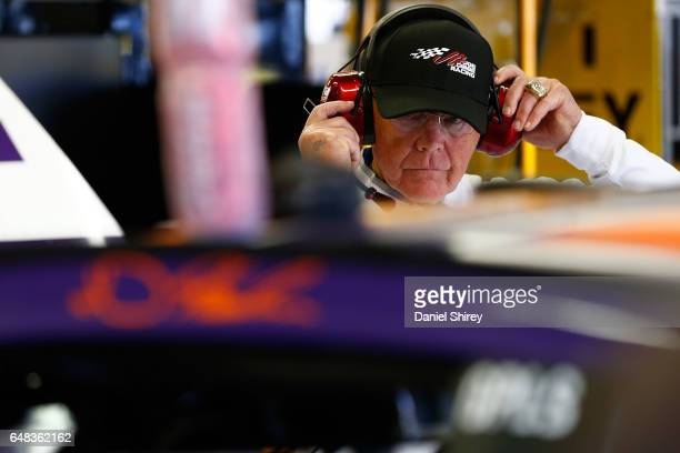 Joe Gibbs team owner for Denny Hamlin driver of the FedEx Ground Toyota stands in the garage after an on track incident during the Monster Energy...