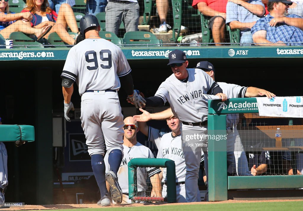Joe Girardi #28 of the New York Yankees congratulates Aaron Judge #99 for scoring in the sixth inning against the Texas Rangers at Globe Life Park in Arlington on September 10, 2017 in Arlington, Texas.