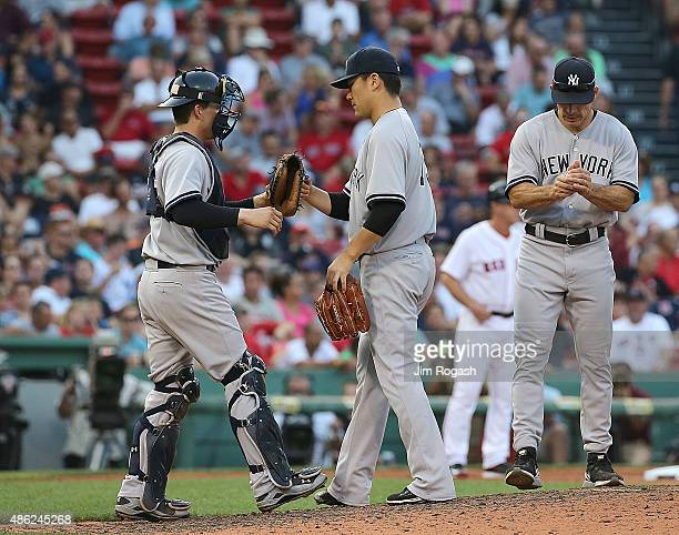 Joe Girardi of the New York Yankees relieves as John Ryan Murphy and Masahiro Tanaka react in the seventh inning against the Boston Red Sox at Fenway...