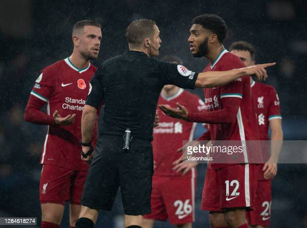 Joe Gomez and Jordan Henderson of Liverpool complain to the referee Craig Pawson fafter he awards a penalty for handball during the Premier League...