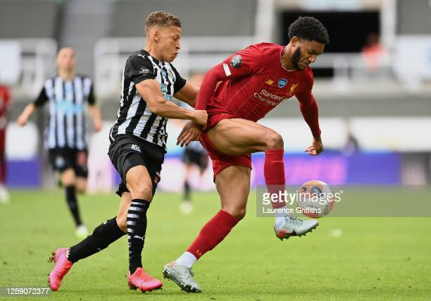 Joe Gomez of Liverpool and Dwight Gayle of Newcastle United compete for the ball during the Premier League match between Newcastle United and...