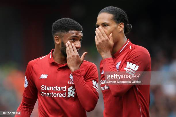 Joe Gomez of Liverpool and Virgil van Dijk of Liverpool cover their mouths as they whisper to each other during the Premier League match between...