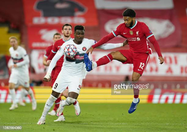 Joe Gomez of Liverpool controls the ball in the air as Sory Kaba of FC Midtjylland looks on during the UEFA Champions League Group D stage match...