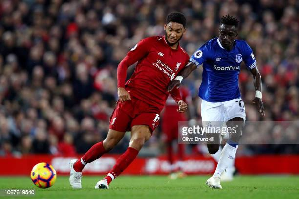 Joe Gomez of Liverpool passes the ball under pressure from Idrissa Gueye of Everton during the Premier League match between Liverpool FC and Everton...