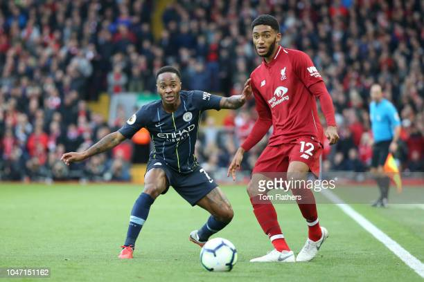 Joe Gomez of Liverpool passes the ball under pressure from Raheem Sterling of Manchester City during the Premier League match between Liverpool FC...