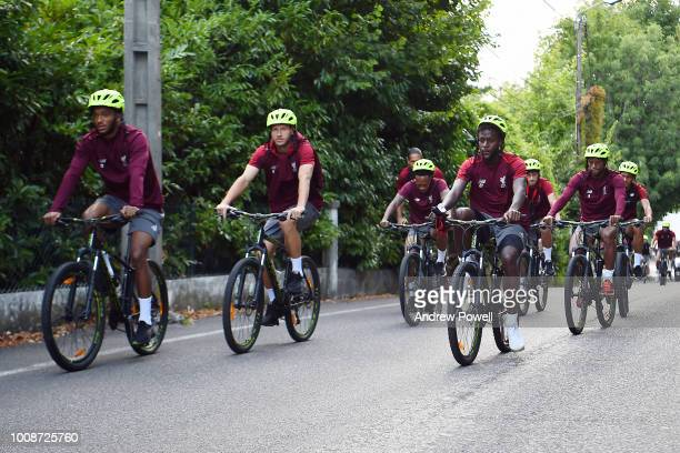 Joe Gomez Ragnar Klavan Divock Origi and Georginio Wijnaldum of Liverpool rinding bikes on thier way to a training session at Ville dEvian on August...