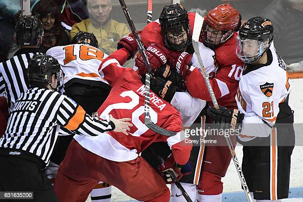 Joe Grabowski of the Princeton Tigers keeps Alec McCrea of the Cornell Big Red in a front headlock as Beau Starrett of the Cornell Big Red tries to...