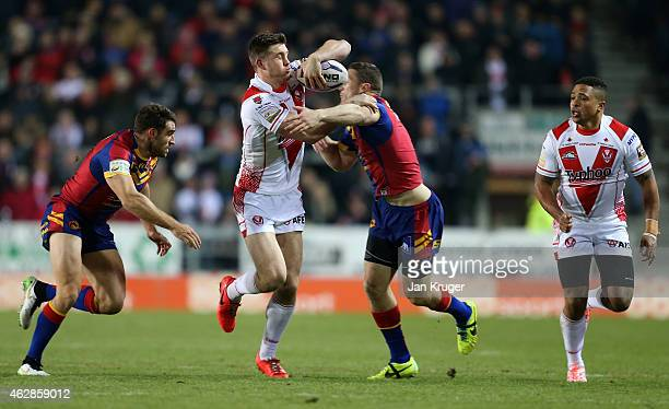 Joe Greenwood of St Helens crashes through the tackle of Ben Pomeroy and Thomas Bosc of Catalans Dragons during the First Utility Super League match...