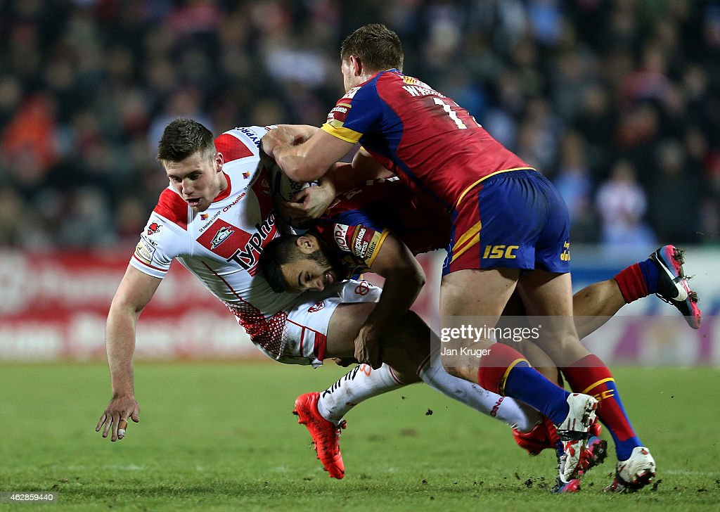 Joe Greenwood of St Helens is dumped by Eloi Pelissier and Elliott Whitehead of Catalans Dragons during the First Utility Super League match between St Helens and Catalans Dragons at Langtree Park on February 6, 2015 in St Helens, England.