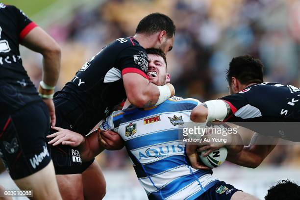 Joe Greenwood of the Titans is tackled by Bodene Thompson and Shaun Johnson of the Warriors during the round five NRL match between the New Zealand...