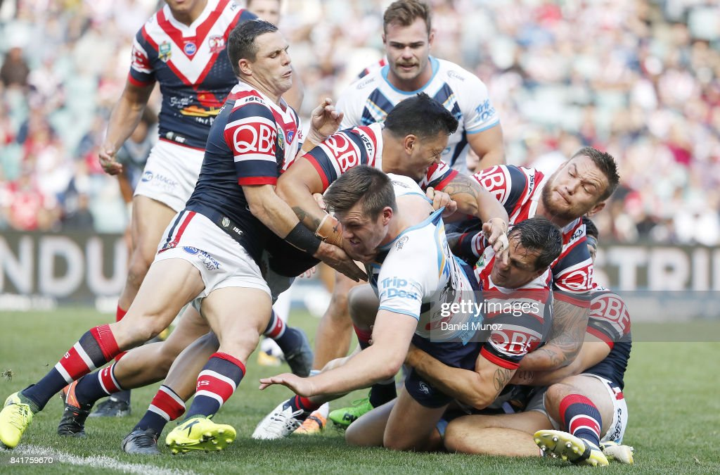 Joe Greenwood of the Titans is tackled by Roosters defence during the round 26 NRL match between the Sydney Roosters and the Gold Coast Titans at Allianz Stadium on September 2, 2017 in Sydney, Australia.