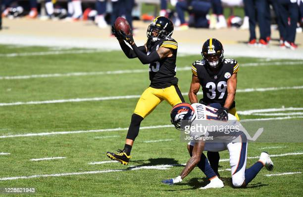 Joe Haden intercepts a pass in front of Minkah Fitzpatrick of the Pittsburgh Steelers and Courtland Sutton of the Denver Broncos during the second...