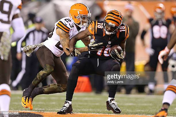 Joe Haden of the Cleveland Browns tackles AJ Green of the Cincinnati Bengals after making a catch during the second quarter at Paul Brown Stadium on...