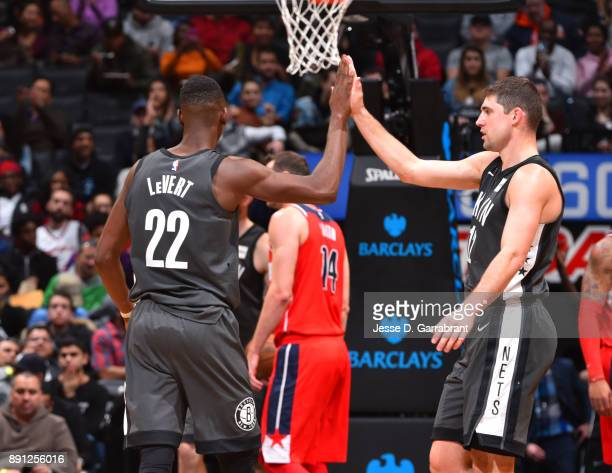 Joe Harris and Caris LeVert of the Brooklyn Nets give each other high fives against the Washington Wizards on December 12 2017 at Barclays Center in...