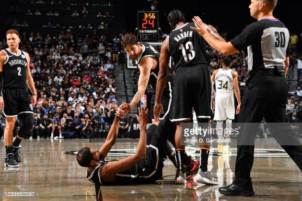 Joe Harris of the Brooklyn Nets and James Harden of the Brooklyn Nets help up Kevin Durant of the Brooklyn Nets during Round 2, Game 7 on June 19,...