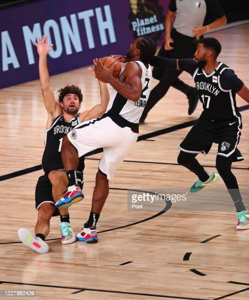 Joe Harris of the Brooklyn Nets is knocked down by Kawhi Leonard of the LA Clippers in the first half of a NBA basketball game at AdventHealth Arena...