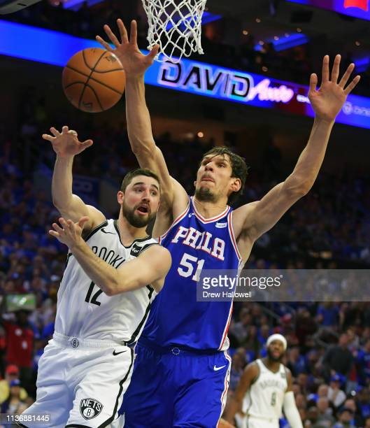 Joe Harris of the Brooklyn Nets passes the ball in front of Boban Marjanovic of the Philadelphia 76ers in the first half during Game One of the first...
