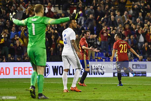 Joe Hart and Ryan Bertrand of England react as Santi Cazorla of Spain celebrates with Juan Mata as he scores their second goal during the...