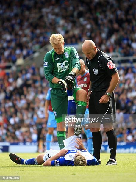 Joe Hart of Birmingham City helps Franck Queudrue relieve his cramp