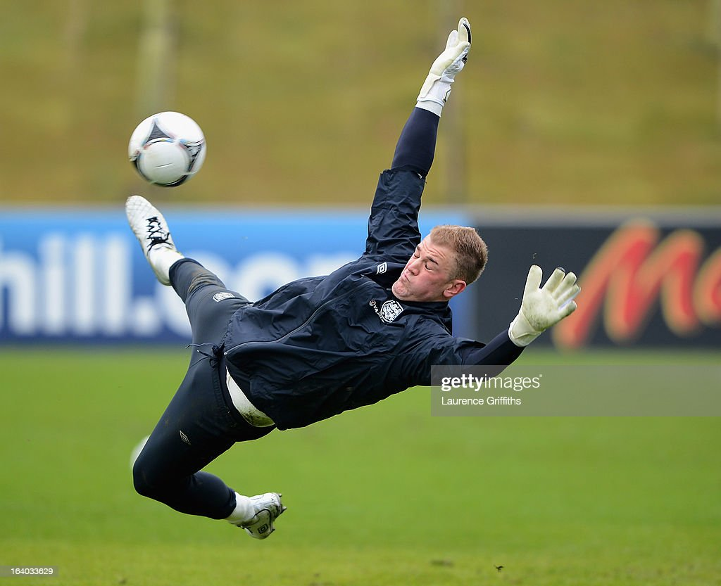 Joe Hart of England dives to save a ball during a training session at St Georges Park on March 19, 2013 in Burton-upon-Trent, England.
