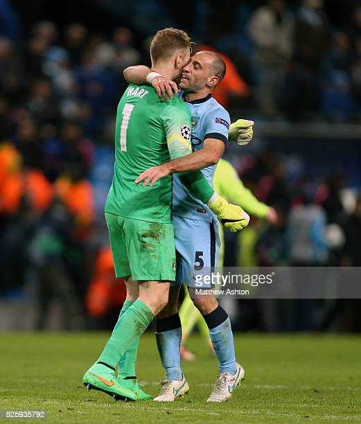 Joe Hart of Manchester City celebrates his penalty save from Lionel Messi of FC Barcelona with Pablo Zabaleta of Manchester City