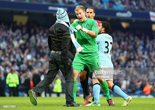 Joe Hart of Manchester City confronts a pitch invader during the Barclays Premier League match between Manchester City and Manchester United at the...