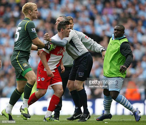 Joe Hart of Manchester City holds back Joey Barton of Queens Park Rangers after he is sent off