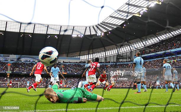 Joe Hart of Manchester City looks on as Laurent Koscielny of Arsenal turns to celebrate after scoring their first goal during the Barclays Premier...